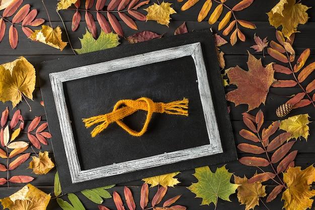 Composição criativa de outono ainda vida, moldura feita de folhas de outono e cachecol,