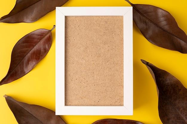 Composição criativa de outono foto branca moldura de folhas secas em fundo amarelo