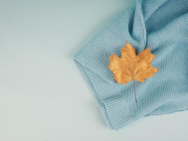 Composição criativa de outono plana leiga. folha dourada sobre suéter