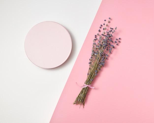Composição criativa de tábua redonda e ramo de flores de lavanda natural em um rosa cinza claro duotônico com espaço de cópia.