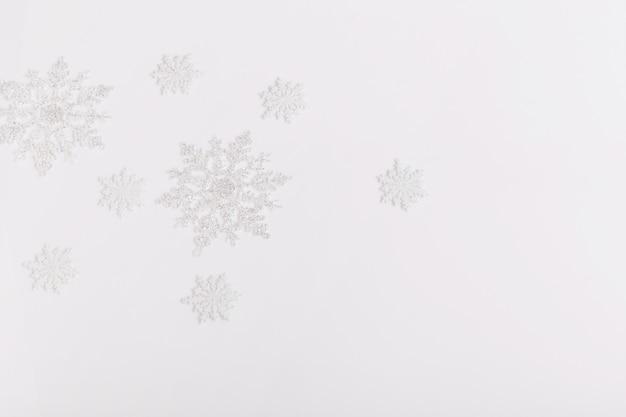 Composição criativa festiva de férias de natal branco, flocos de neve de férias de decoração de natal em fundo cinza pastel. natal, inverno, conceito de ano novo. camada plana, vista superior, espaço de cópia