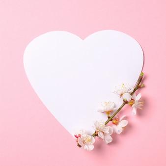 Composição criativa leiga plana: papel em forma de coração e ramo de sakura floresce