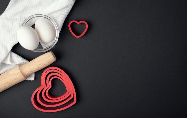 Composição culinária do dia dos namorados. formas vermelhas em forma de coração, rolo, tigela de ovos e pano de prato no fundo escuro (preto).
