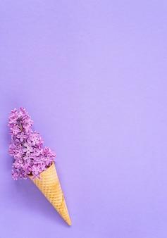 Composição da casquinha de sorvete com as flores lilás roxas em um fundo violeta. configuração plana. vista do topo. conceito criativo de verão