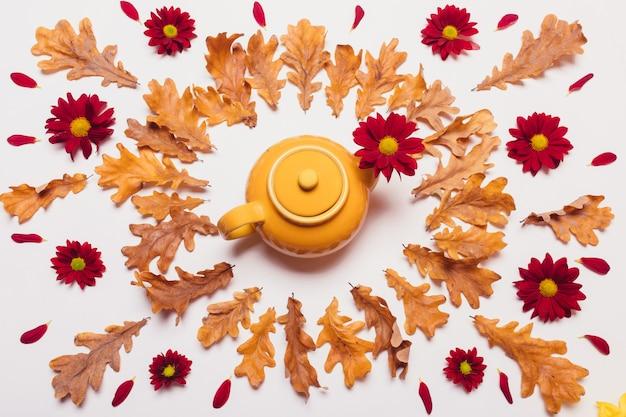Composição da chaleira amarela, folhas secas e flores vermelhas com pétalas no fundo branco