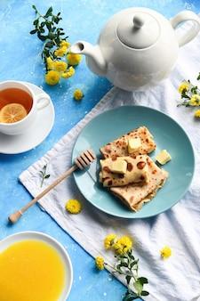 Composição da mesa do café. panquecas, chá, mel, decoração, superfície azul