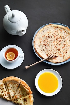 Composição da mesa do café. panquecas, chá, mel, superfície escura