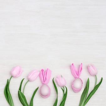 Composição da páscoa com os ovos da páscoa cor-de-rosa feitos a mão com as orelhas do coelho e da tulipa das flores frescas em de madeira branco com espaço da cópia. vista de cima, plana leigos.