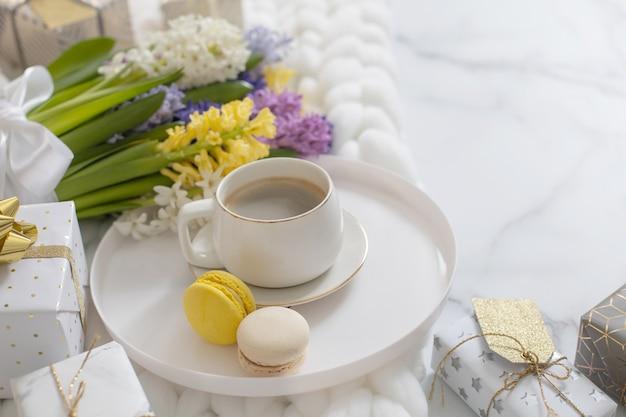 Composição da vista superior com uma xícara de macarons de massa de café e jacinto multicolorido primavera em manta de malha branca fofa