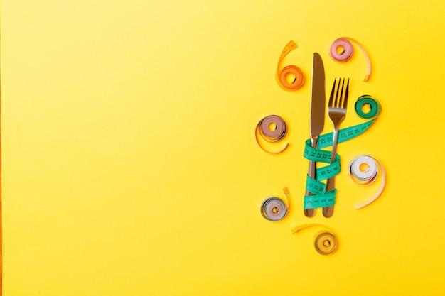 Composição da vista superior da forquilha e da faca com as fitas de medição balled coloridas no fundo amarelo com espaço vazio para suas ideias. conceito de excesso de peso e excessos