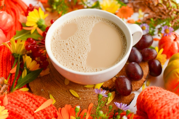 Composição da xícara de café de outono. uvas, folhas de outono, flores