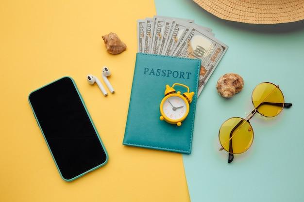 Composição das férias de verão. óculos de sol, smartphone, chapéu e passaporte com notas de dinheiro na superfície azul amarela
