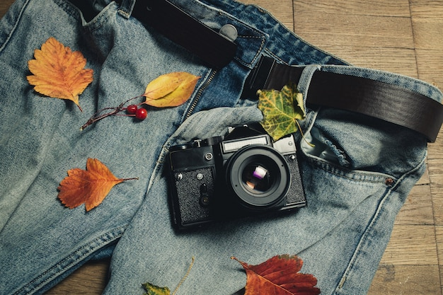 Composição das folhas de outono, da câmera retro e da calças de ganga no fundo de madeira.