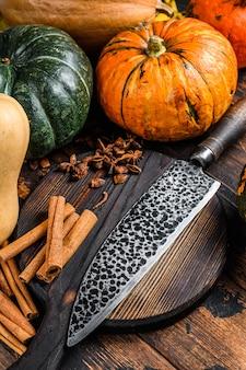 Composição de alimentos com abóboras, faca e tábua de cortar. fundo de madeira escuro. vista do topo.
