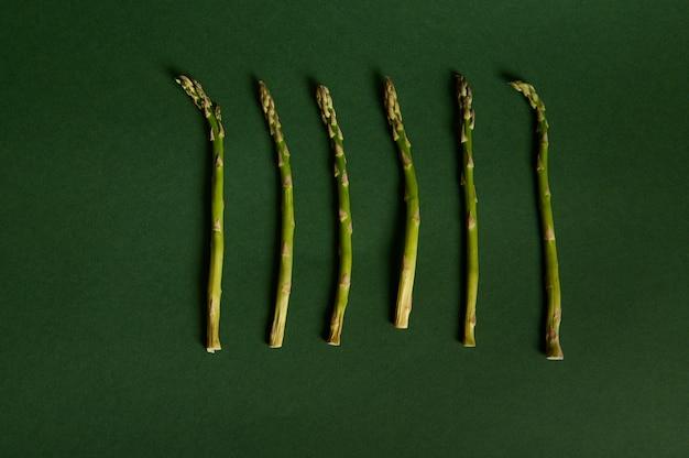 Composição de alimentos plana leiga monocromática de espargos crus orgânicos verdes sobre fundo verde escuro com espaço de cópia. comida vegana crua saudável