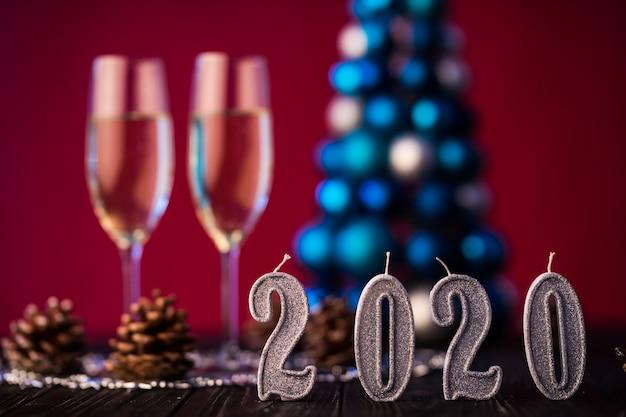 Composição de ano novo 2020 com champanhe e espaço para texto contra árvore e luzes de natal borradas. conceito de ano novo e natal
