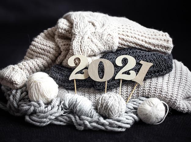 Composição de ano novo com itens de malha e número de ano novo de madeira em um fundo escuro close-up.