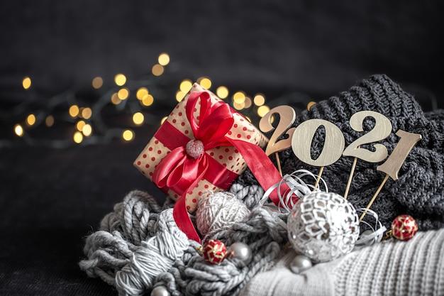 Composição de ano novo com número de ano novo de madeira e decorações de natal em um fundo escuro.