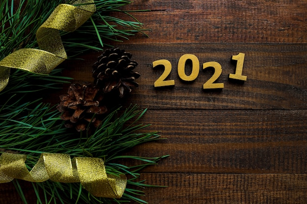 Composição de ano novo com números dourados 2021 com ramos de pinheiro, pinhas e fitas douradas