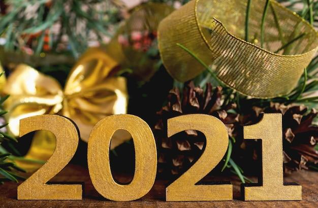 Composição de ano novo com números dourados 2021, fita dourada e arco e pinhas
