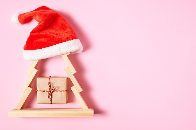 Composição de ano novo de caixa de madeira para árvore de natal e chapéu de papai noel em papel rosa com espaço de cópia