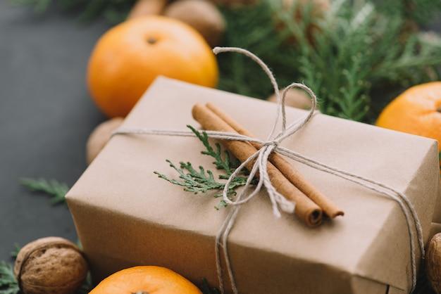 Composição de ano novo de natal com caixas de tangerinas cones de pinheiro verdes em decoração de férias de fundo preto em tons