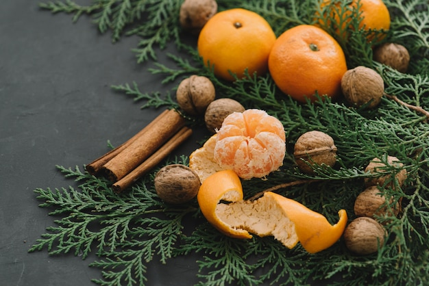Composição de ano novo de natal com tangerinas cones de pinheiro canela de nozes verdes sobre ...