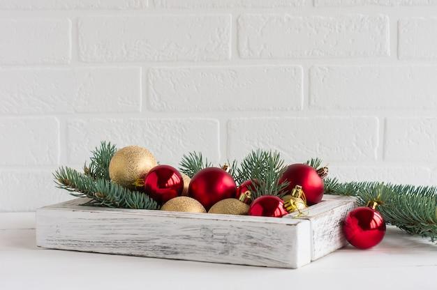 Composição de ano novo ou natal. caixa de madeira branca com bolas vermelhas e douradas de natal, ramos de abeto em uma mesa de madeira em frente à parede de tijolos.