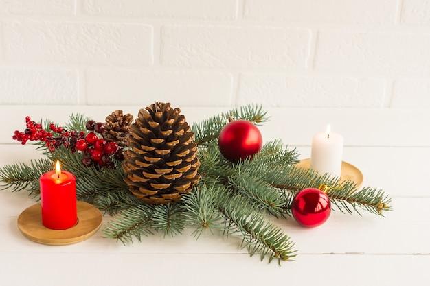 Composição de ano novo para decorar a mesa e a casa festiva. ramos de abeto, um ramo com bagas, uma vela, bolas e um cone de cedro.