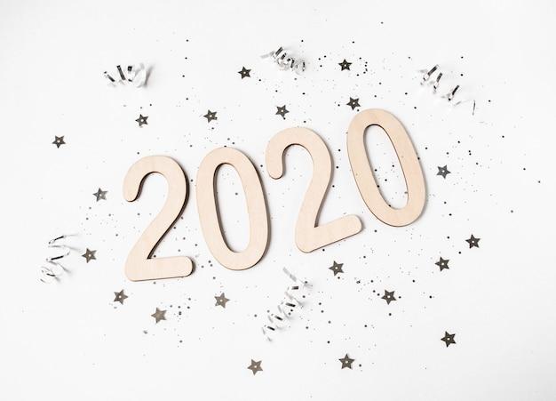 Composição de ano novo plana leiga branca - números 2020 e confetes. vista do topo