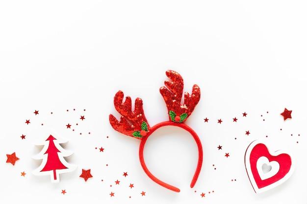 Composição de arte de natal com enfeites vermelhos, tiara de rena na superfície branca. conceito de celebração de natal. camada plana, vista superior, cópia espaço, cartão comemorativo