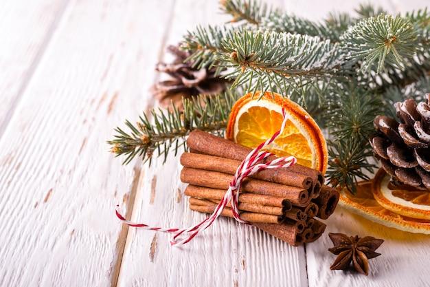 Composição de atmosfera de natal com canela e laranjas secas em fundo branco de madeira