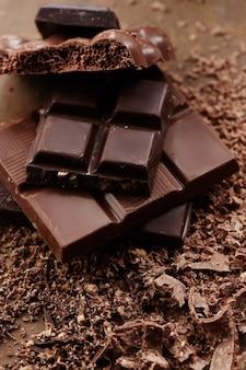 Composição de barras e pedaços de diferentes leite e chocolate amargo, cacau ralado em um fundo marrom vista superior close-up