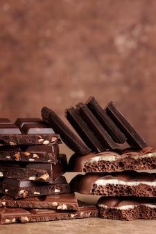 Composição de barras e pedaços de leite diferente e chocolate escuro poroso com nozes e coco em uma vista lateral close-up de fundo marrom