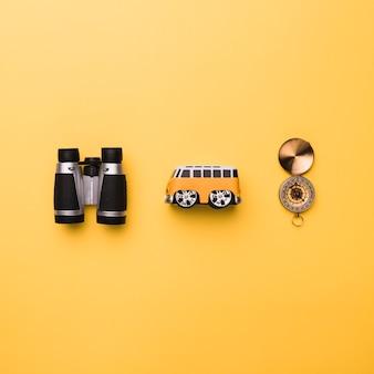 Composição de binóculos pequeno brinquedo ônibus e bússola