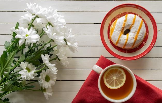 Composição de bolo de bom dia e flores de chá em uma vista superior de fundo branco de madeira