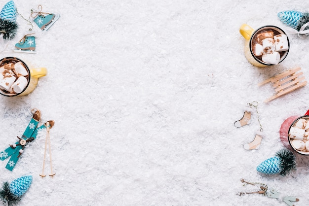 Composição de canecas perto de brinquedos de natal entre a neve