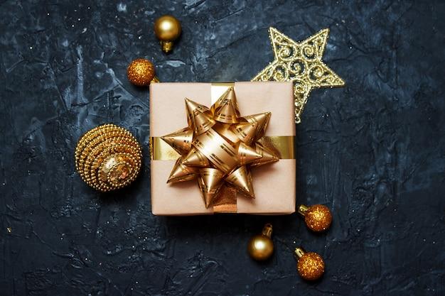 Composição de cartão de natal. presente com decoração de natal dourada sobre fundo azul escuro.