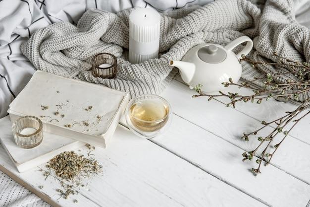 Composição de casa aconchegante com uma xícara de chá de ervas e livros sobre uma superfície de madeira.