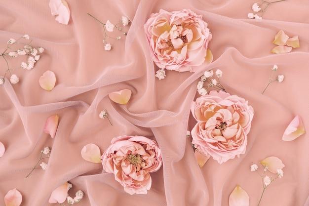 Composição de casamento com tecido de tule delicado rosa pastel com pétalas de rosas.
