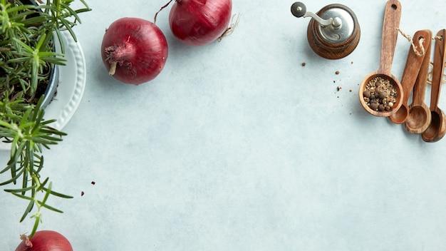 Composição de cebola roxa e especiarias na vista superior da mesa da cozinha em azul claro