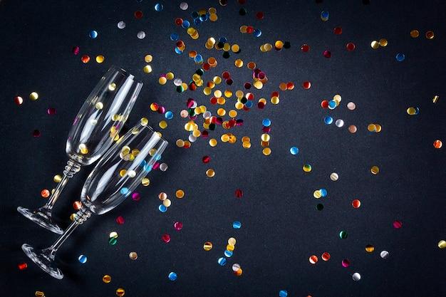 Composição de celebração com copos de champanhe, vinho e confetes na superfície festiva