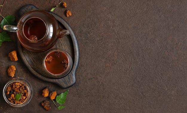 Composição de chá de chaga, pedaços de cogumelo de chaga, folhas de bétula verde sobre fundo marrom. bebida saudável na moda. copie o espaço, vista superior, configuração plana.