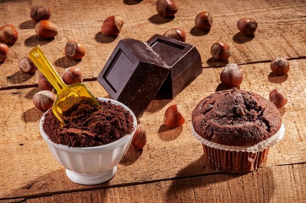 Composição de chocolate, cacau e muffins em uma placa de madeira