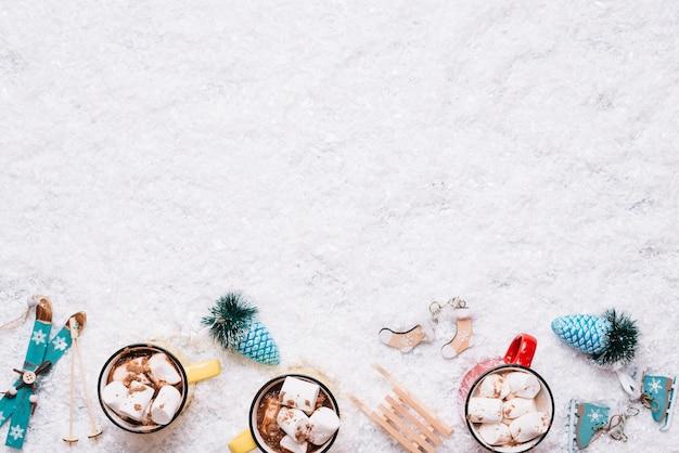 Composição de copos perto de brinquedos de natal entre neve