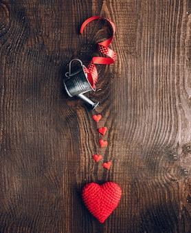 Composição de corações de tecido e baldes decorativos em um fundo escuro de madeira