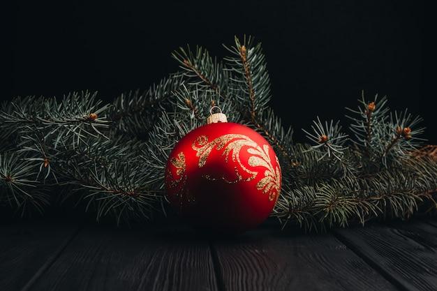Composição de decoração de ano novo de natal. vista superior do quadro de galhos e bolas de árvore de peles no fundo de madeira