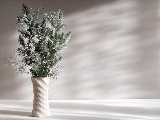 Composição de decoração de inverno em vaso, galhos de pinheiro e gipsófila