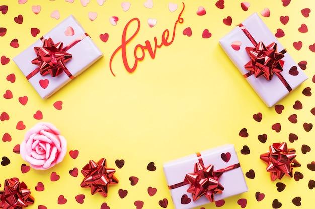 Composição de dia dos namorados, caixa de presente de saudação com corações de confete em fundo amarelo. postura plana.