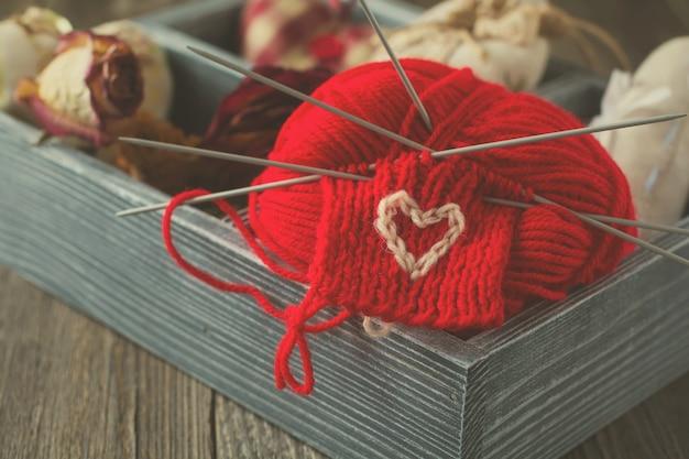 Composição de dia dos namorados com corações tilda, tricô e flores secas em uma caixa de madeira. estilo rústico. imagem tonificada. foco seletivo.